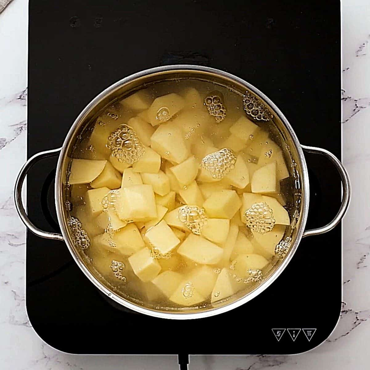 Stock pan with cubed potatoes covered with water.