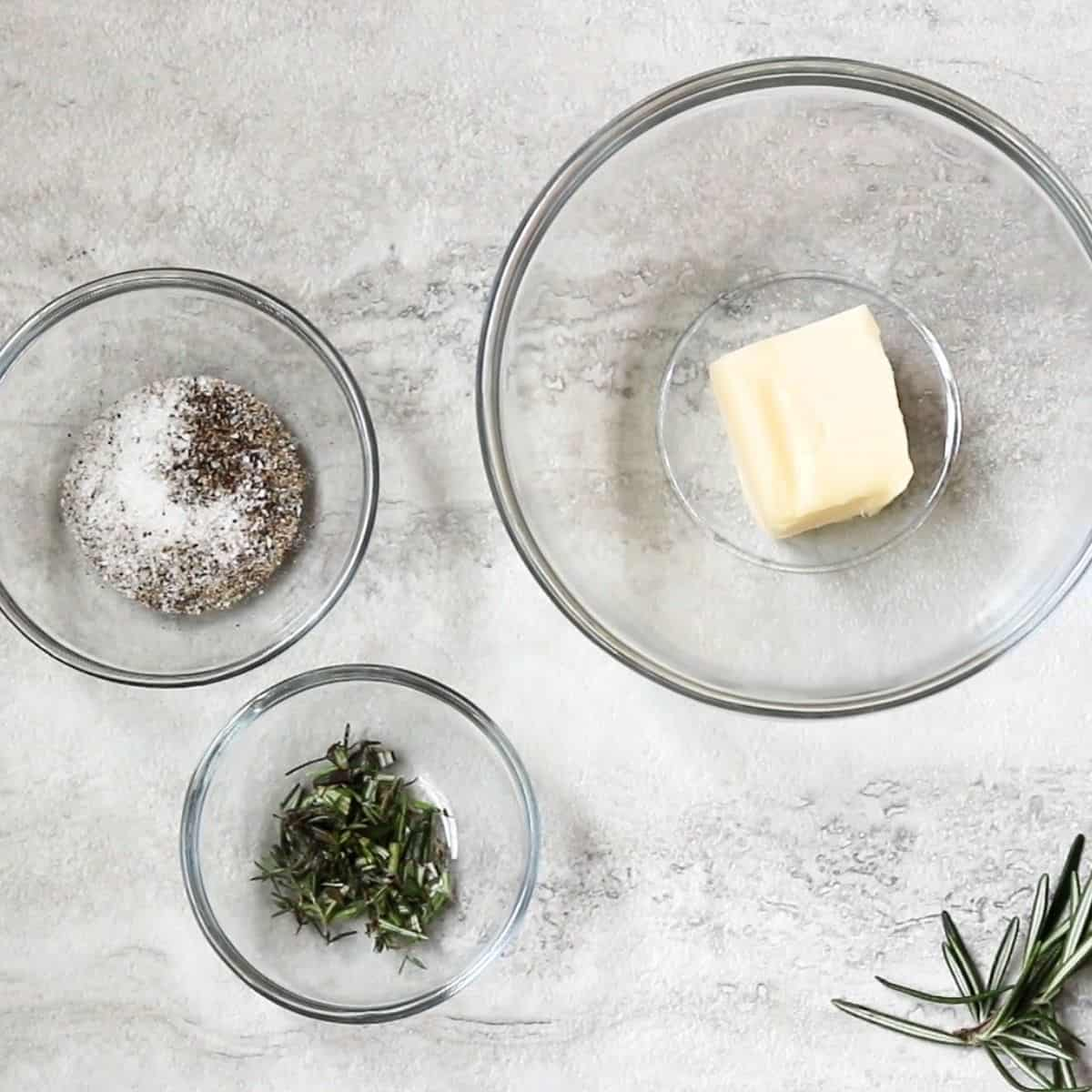 Ingredients for compound butter in glass bowls.