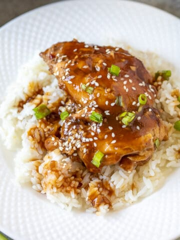 Instant Pot Teriyaki Chicken dished out over white rice on white plate.