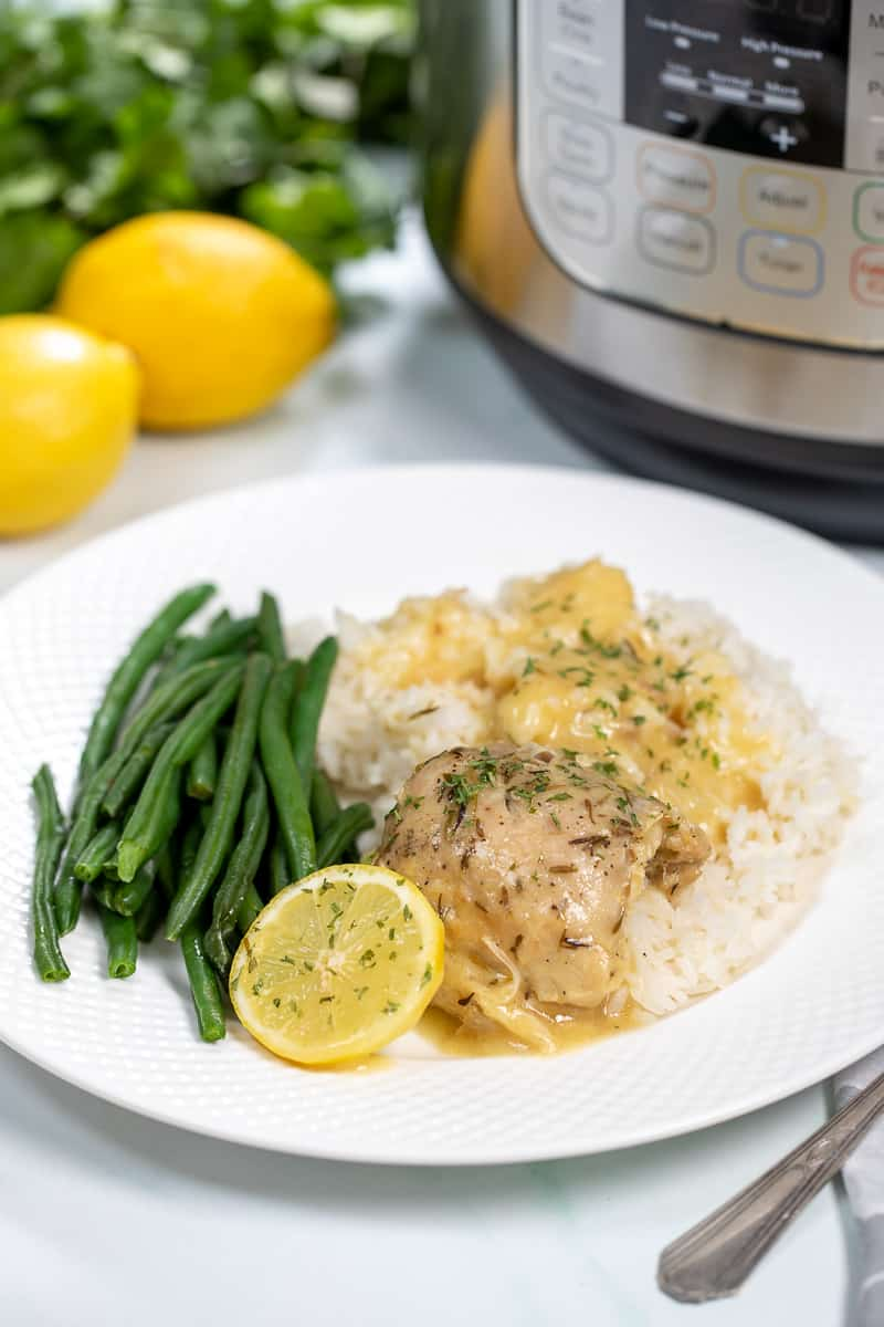 White plate with lemon chicken and green beans next to instant pot.