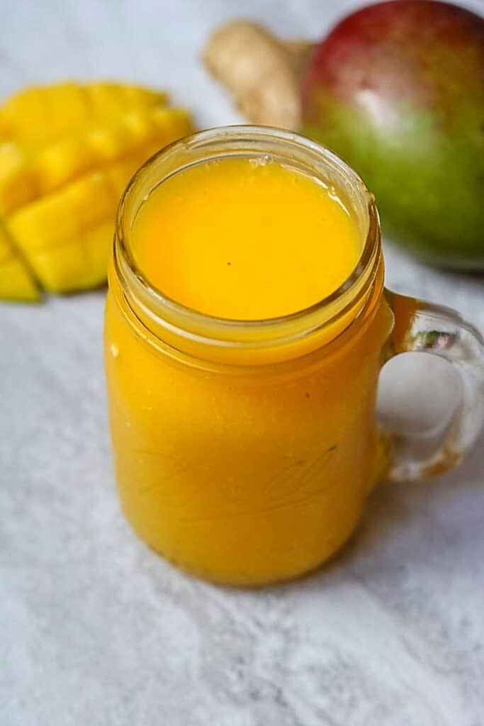 Glass of Mango Smoothie next to fresh mango