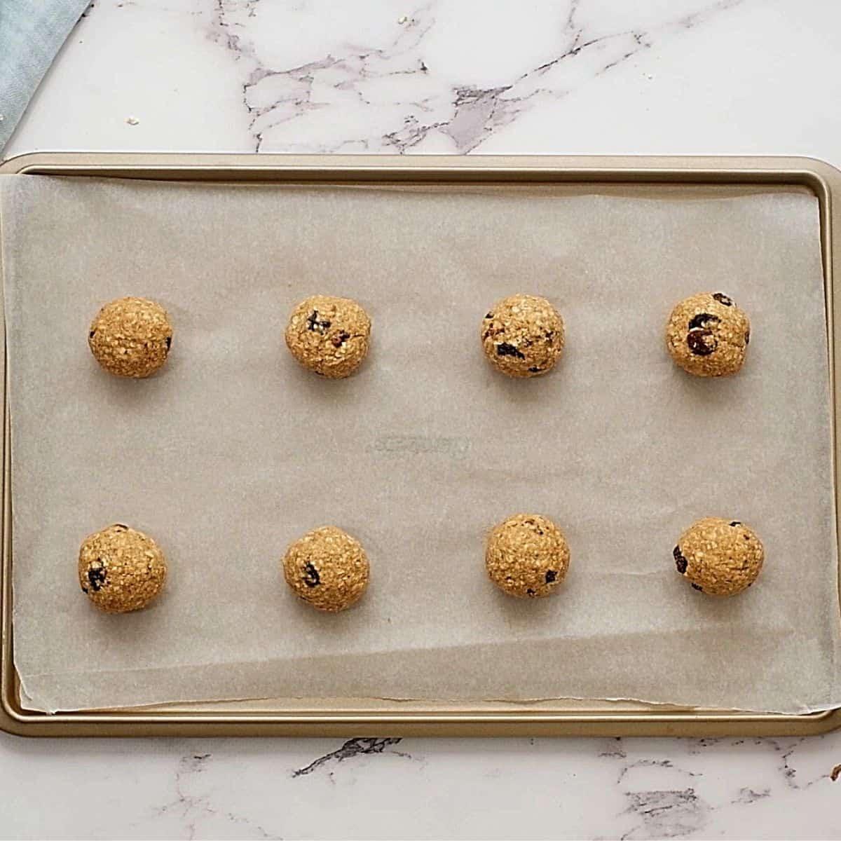 Balls of Oatmeal Raisin Cookie Dough on Baking sheet.