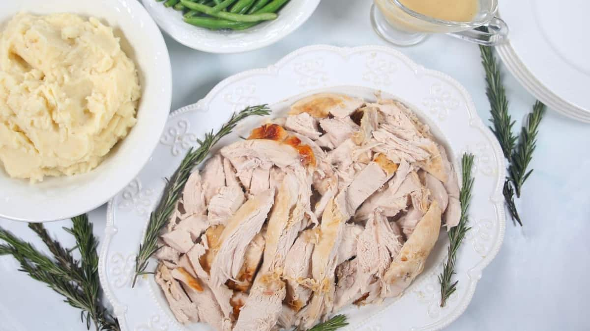 Sliced Turkey Breast on white platter with mashed potatoes and green beans in background.