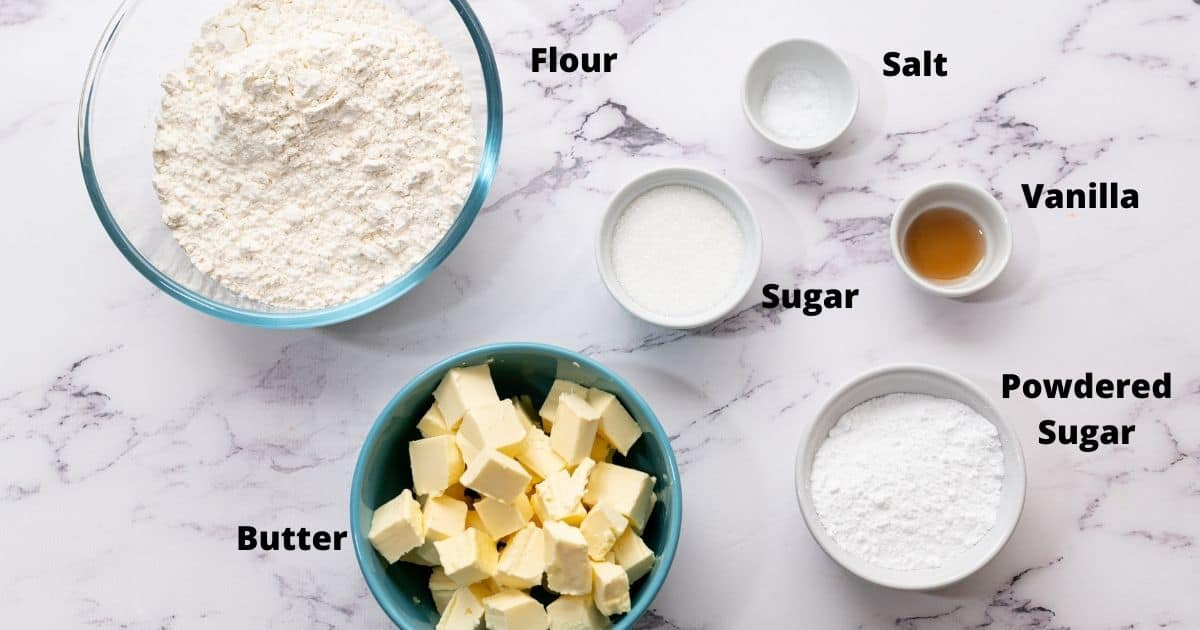 Ingredients for shortbread cookies labeled on white counter.