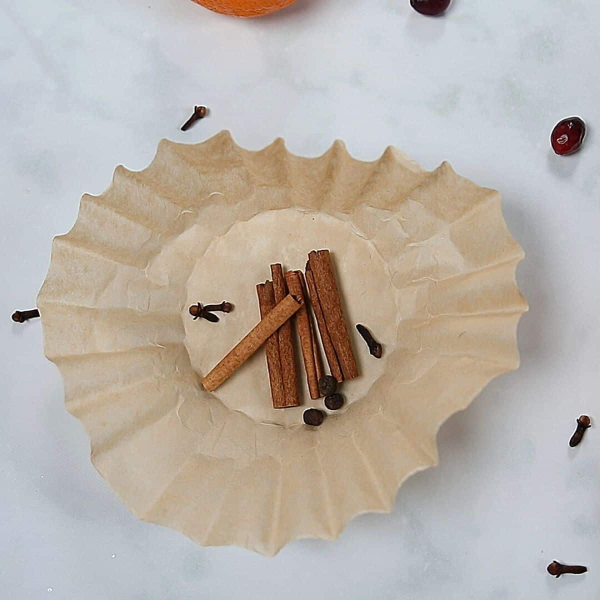 Whole spices on coffee filter.
