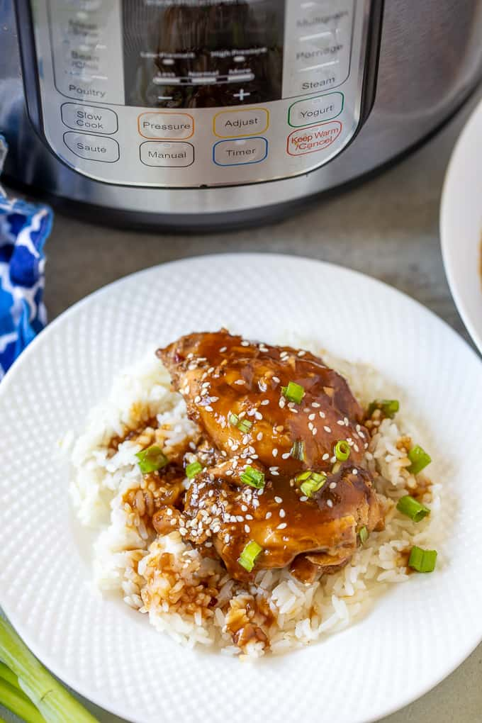 White plate with Instant Pot Teriyaki Chicken over white rice next to instant pot.
