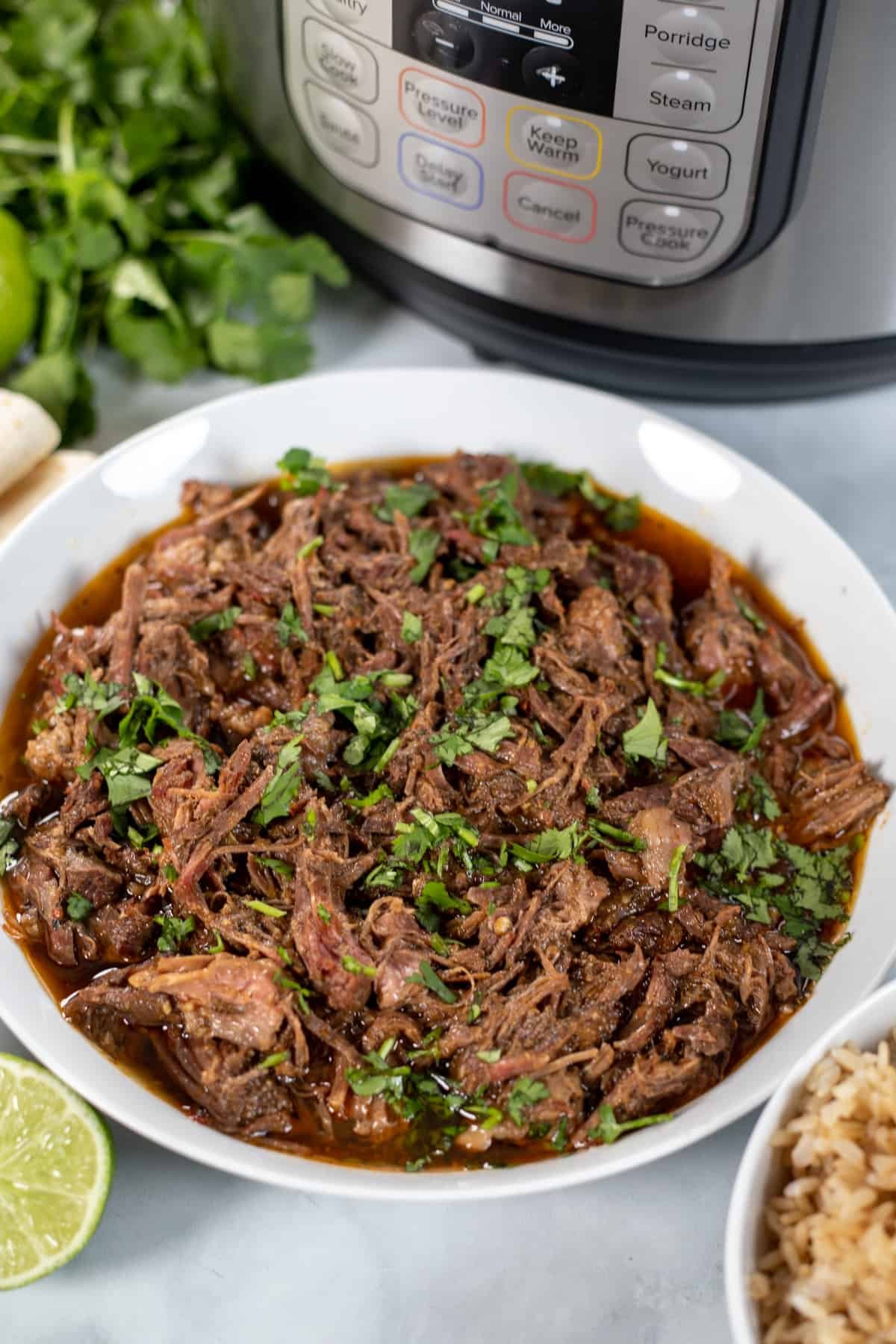 White bowl filled with shredded barbacoa next to instant pot.