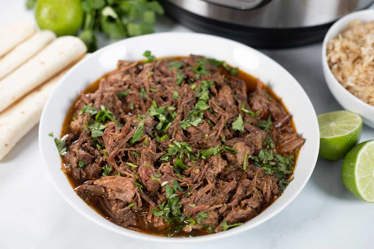 Beef Barbacoa in white bowl next to instant pot.