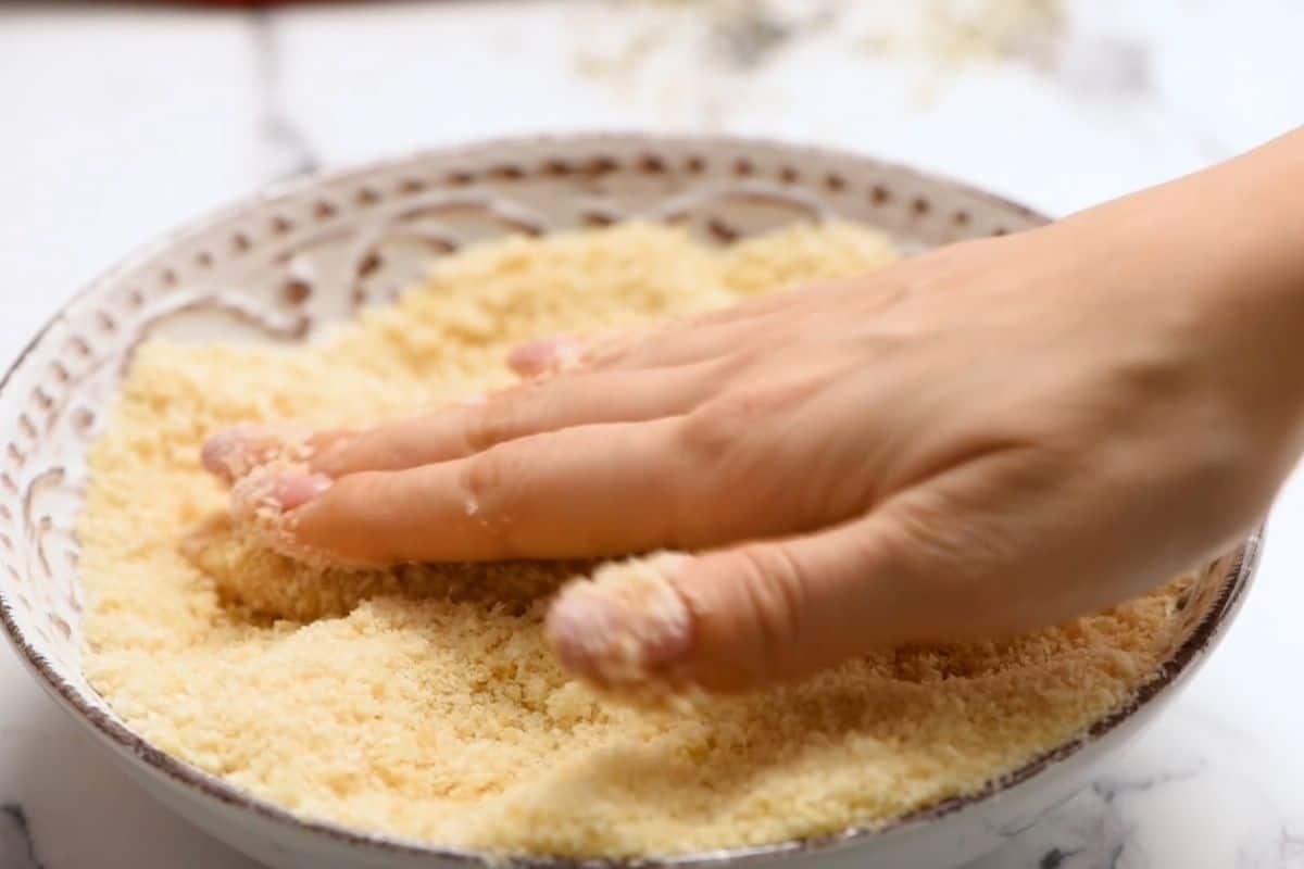 Hand pressing bread crumbs onto chicken tender.