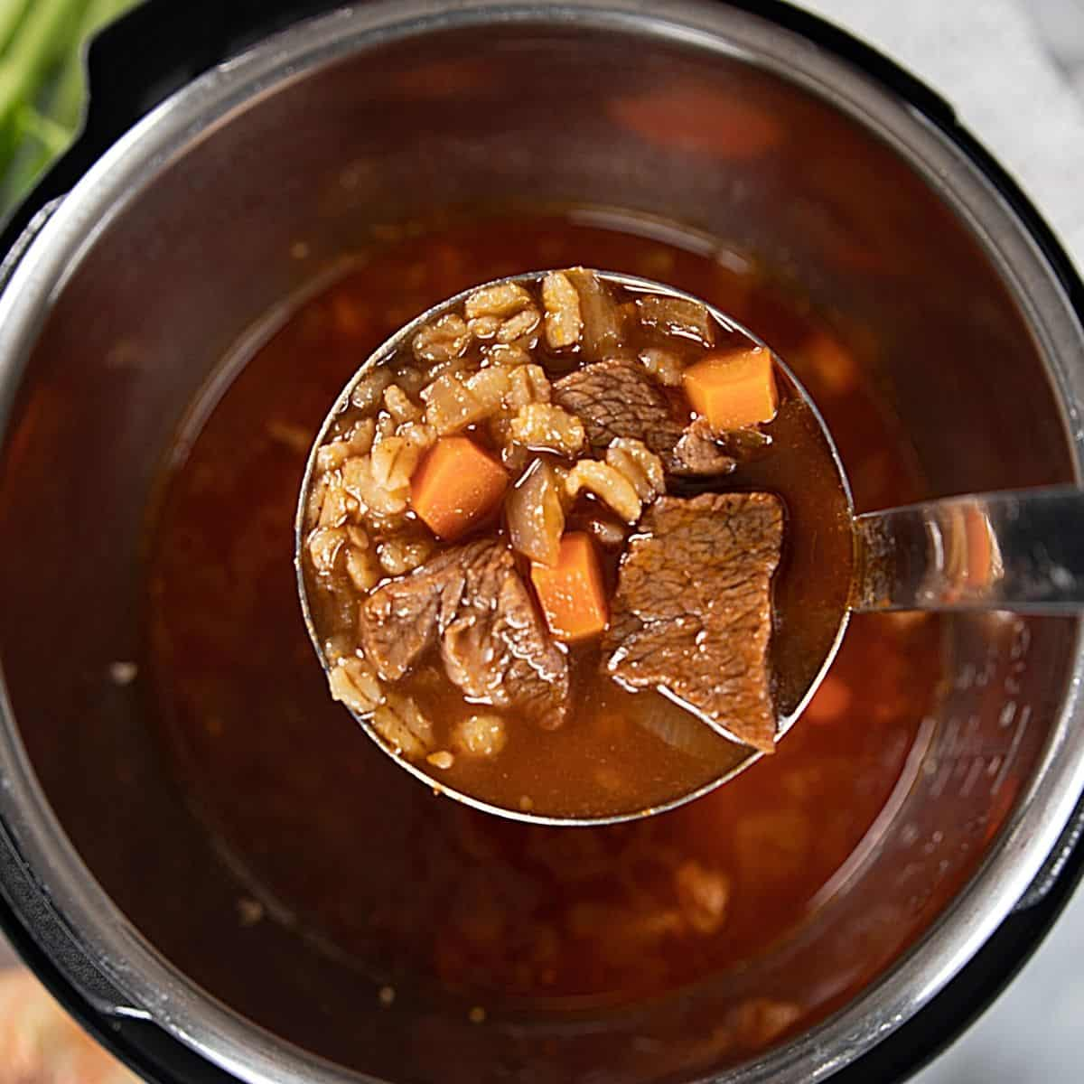Ladle scooping out beef and barley soup from inner pot.