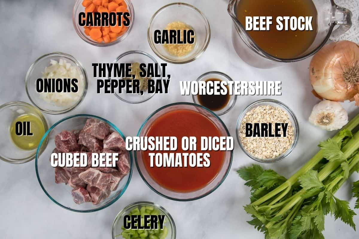 Ingredients for Beef and Barley Soup labeled on white counter.