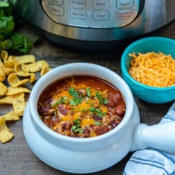 Bowl of chili next to instant pot.