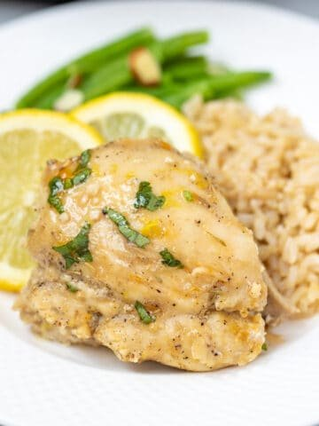 Instant Pot Lemon Chicken Thigh on a white plate next to brown rice.