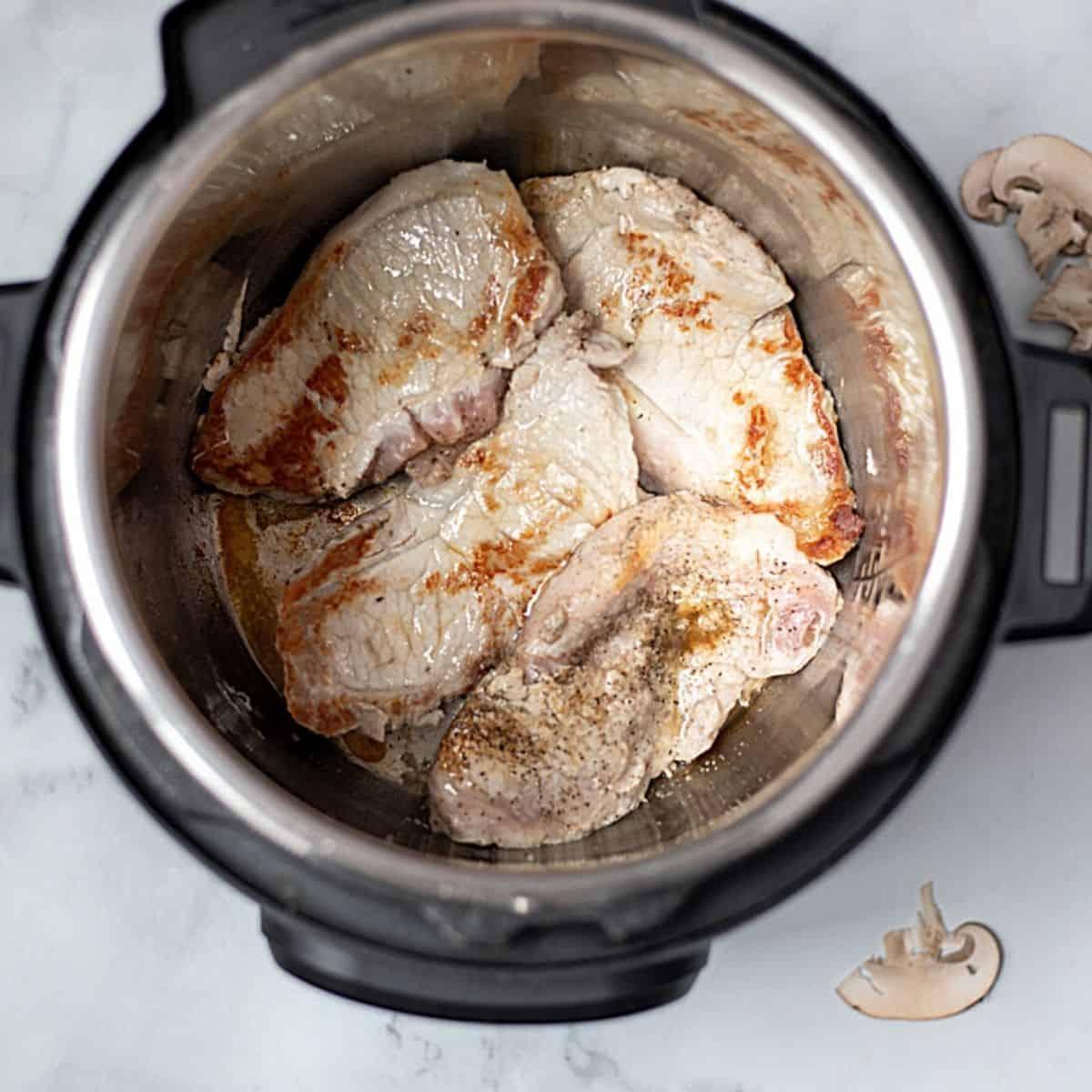 Seared pork chops in inner pot.