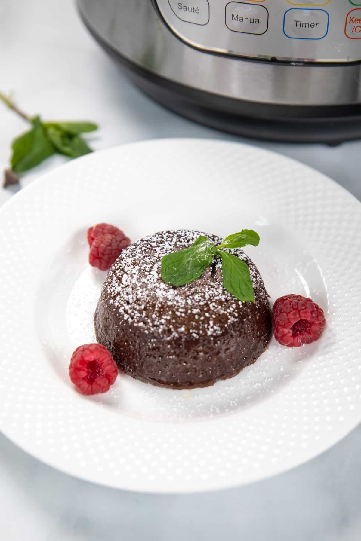 Lava cake on white plate topped with powdered sugar and raspberries.