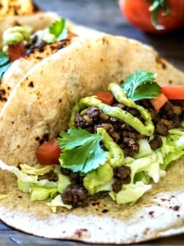 Lentil Taco meat on tortilla topped with avocado and cabbage.