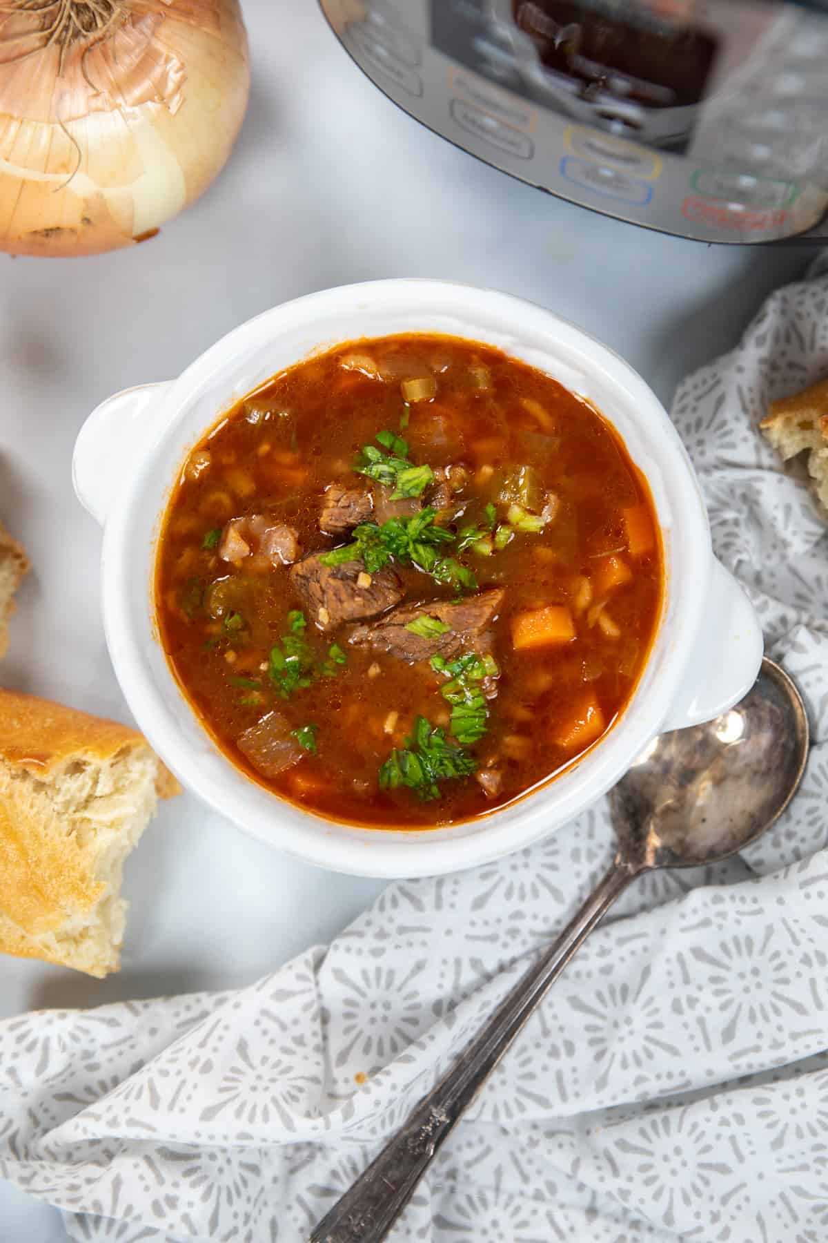 Bowl of Beef and Barley Soup next to instant pot and bread.