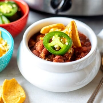Bowl of chili with corn chips next to crockpot.