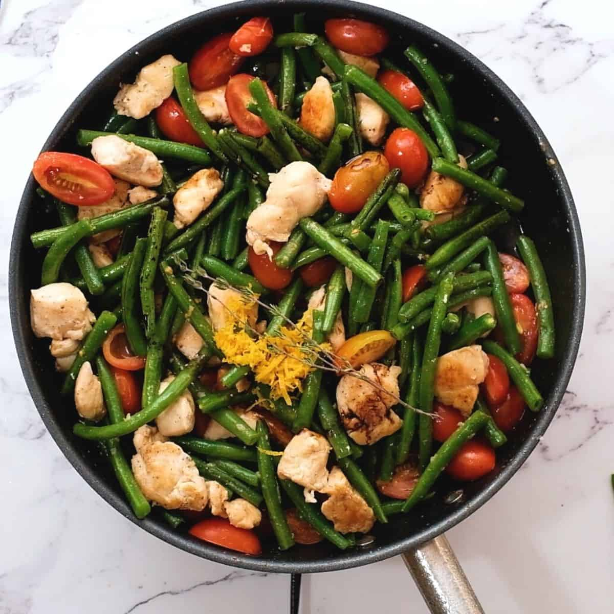 Chicken with tomatoes and green beans in skillet with lemon zest.