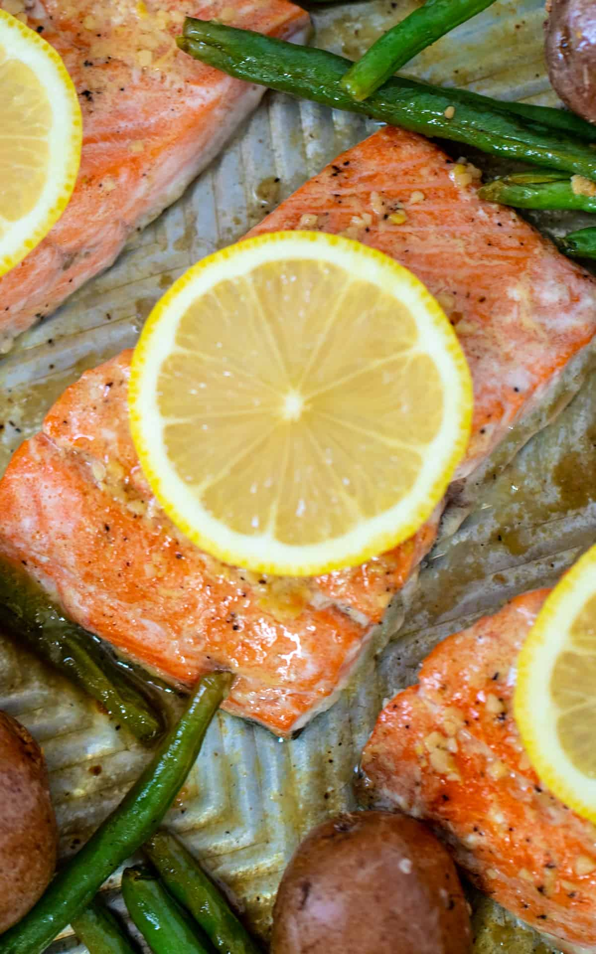 Close of salmon on sheet pan topped with sliced salmon next to green beans and potatoes.