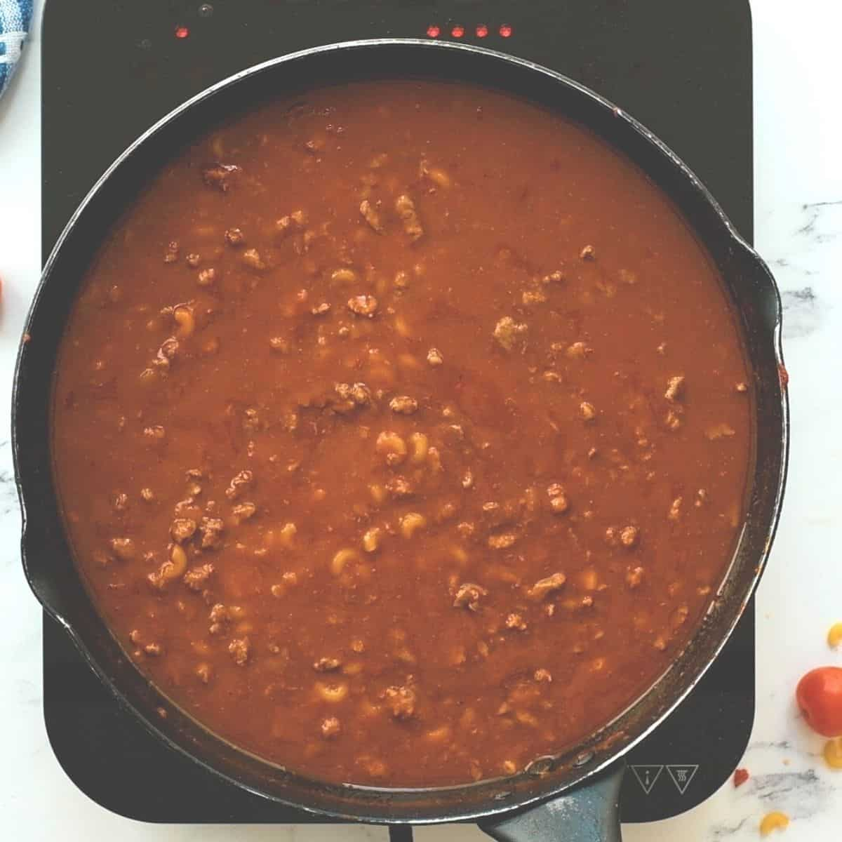 Large skillet with ingredients for hamburger helper simmering in pan.