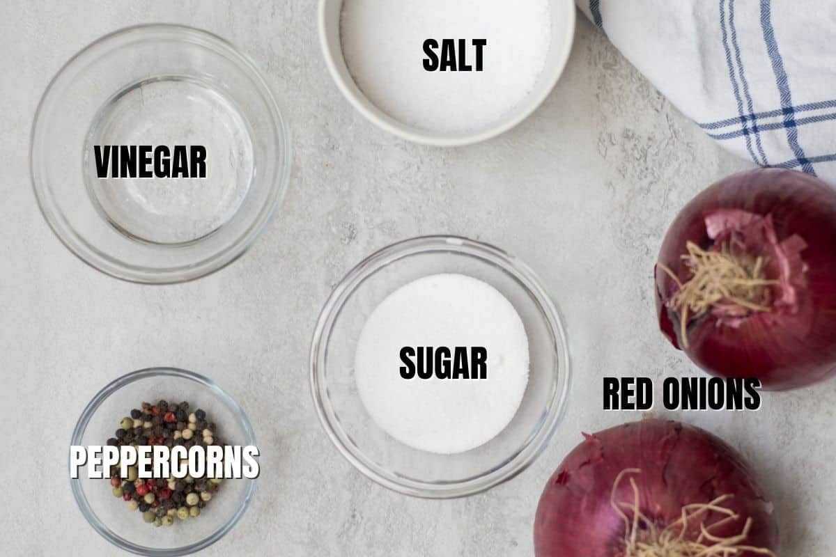 Ingredients for pickled red onions labeled on white counter.