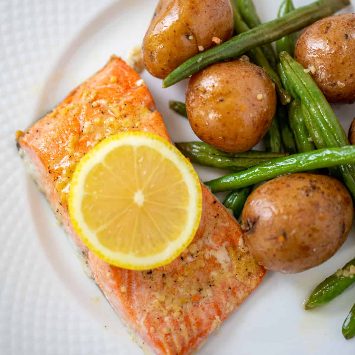 Honey Garlic Salmon on plate with green beans and potatoes to the side.