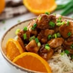 Bowl of orange chicken on top of rice.