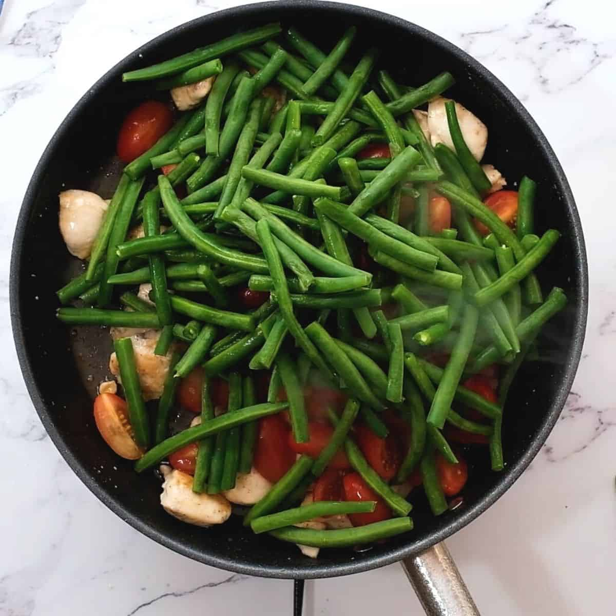 Green beans and tomatoes with chicken in skillet.