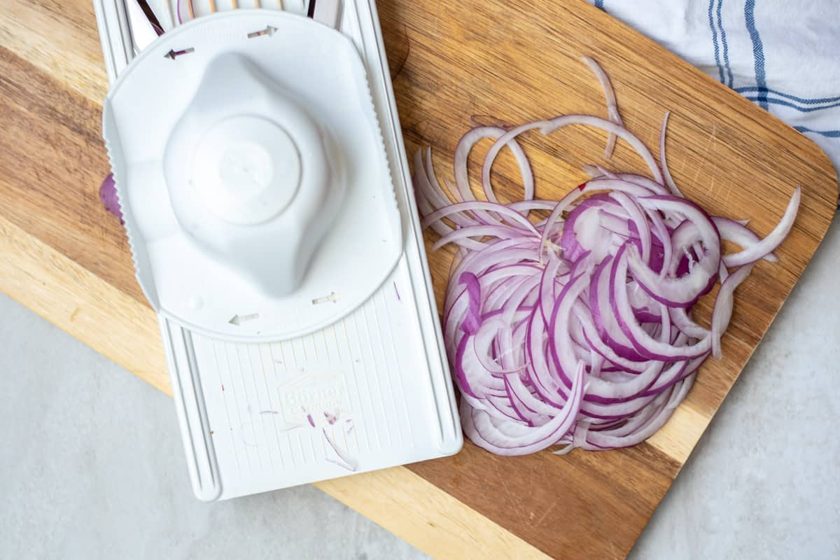Thinly sliced red onions on a cutting board nex to a mandoline.