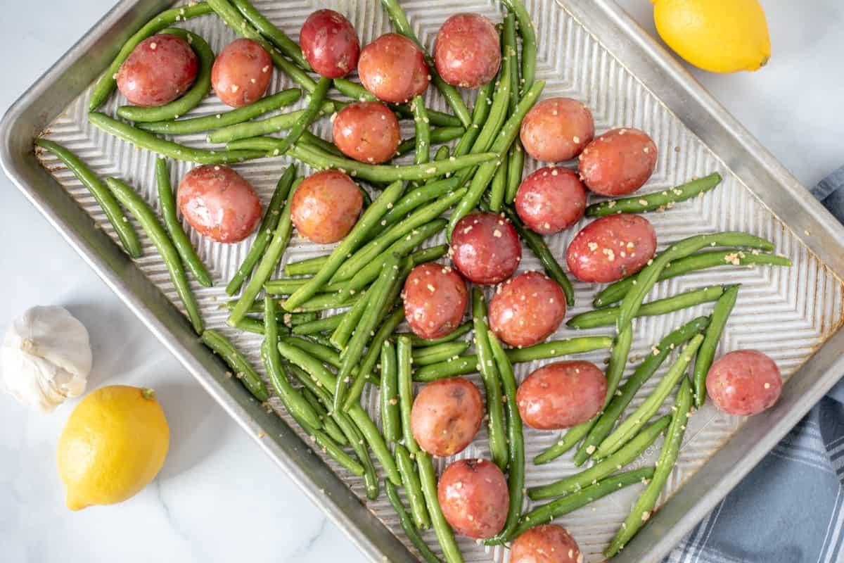 Seasoned potatoes and green beans on sheet pan.