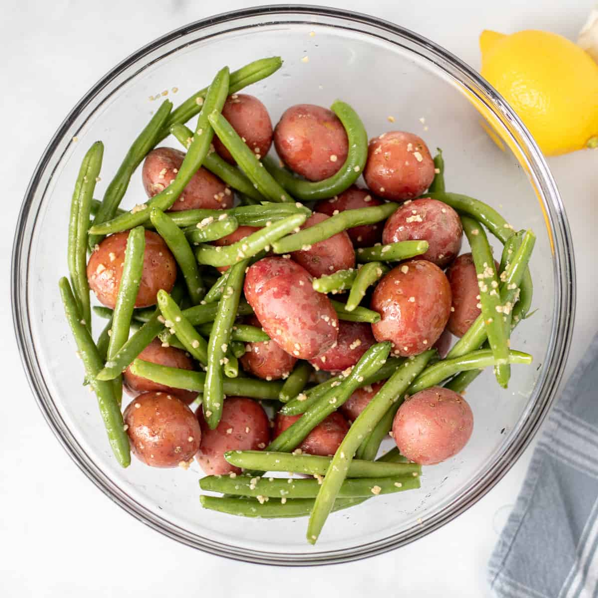 Red potatoes and green beans in clear mixing bowl with garlic and salt and pepper.