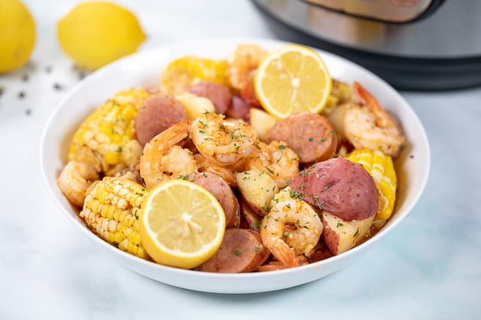 Platter with shrimp boil and fresh lemons and instant pot in background.