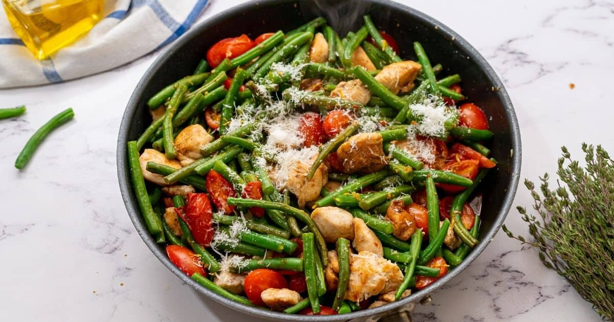 Skillet with chicken, green beans, and tomatoes, cheese.