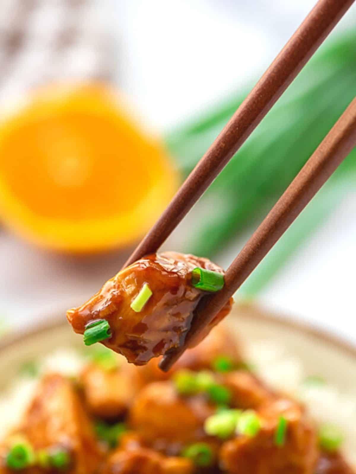 Chopstick holding piece of orange chicken.