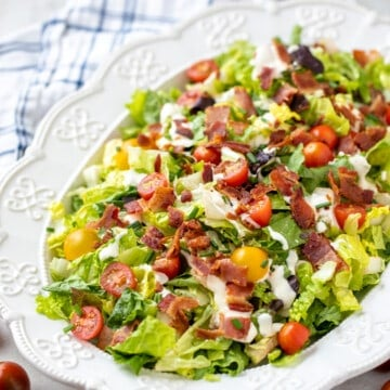 BLT Salad in white platter with next to cherry tomatoes and fresh chives.