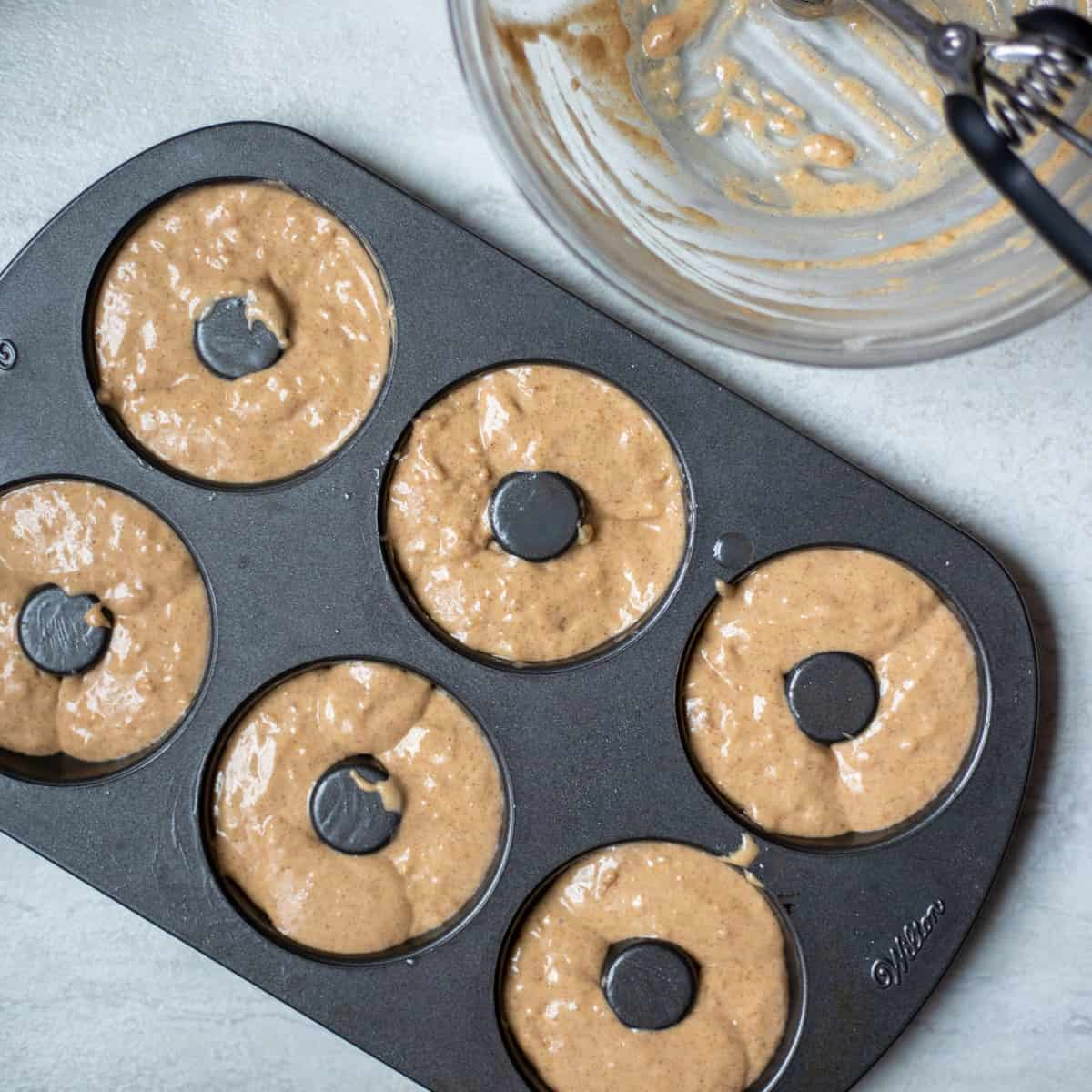 Cinnamon donut batter portioned out into a donut pan.