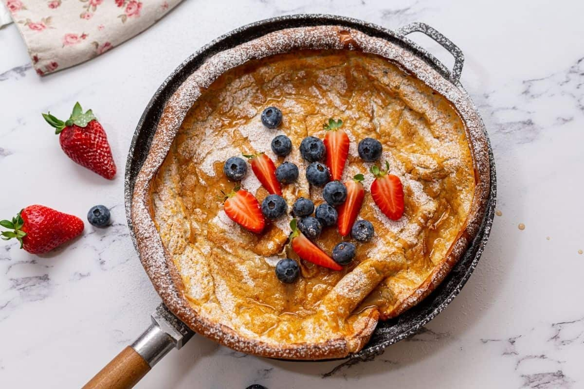 Baked Dutch oven pancake in skillet with berries and maple syrup.