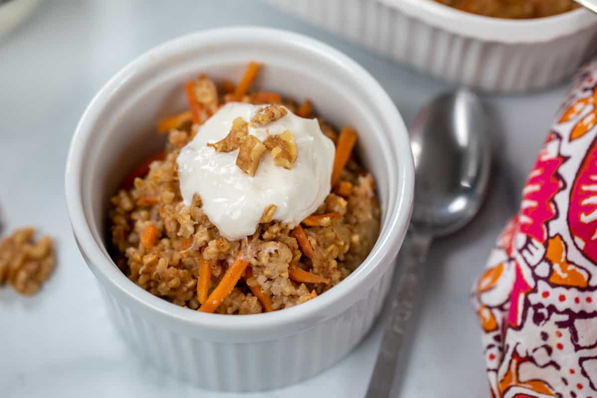Bowl of carrot cake steel cut oats topped with nuts and yogurt.