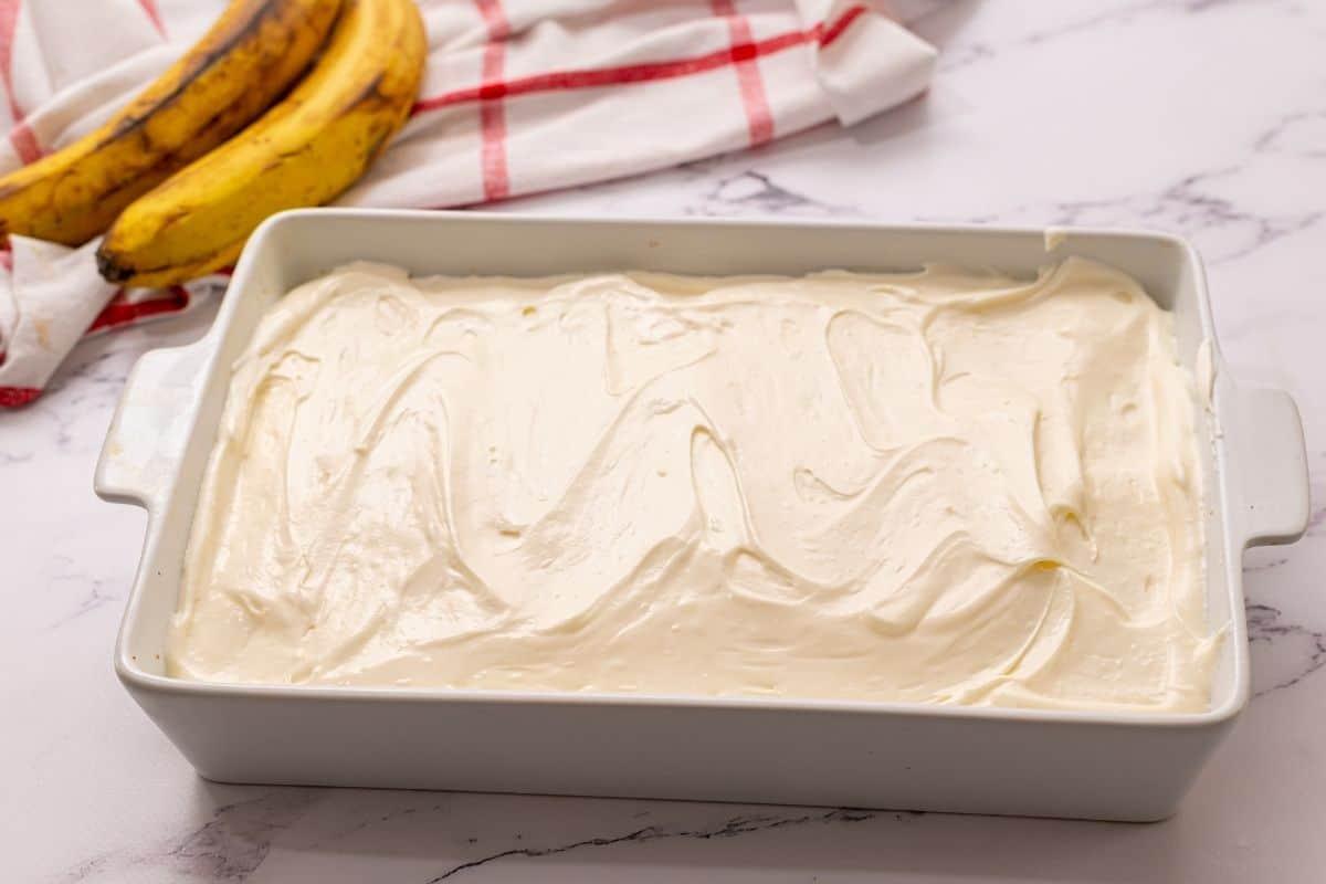 Banana Cake Iced in white cake pan.