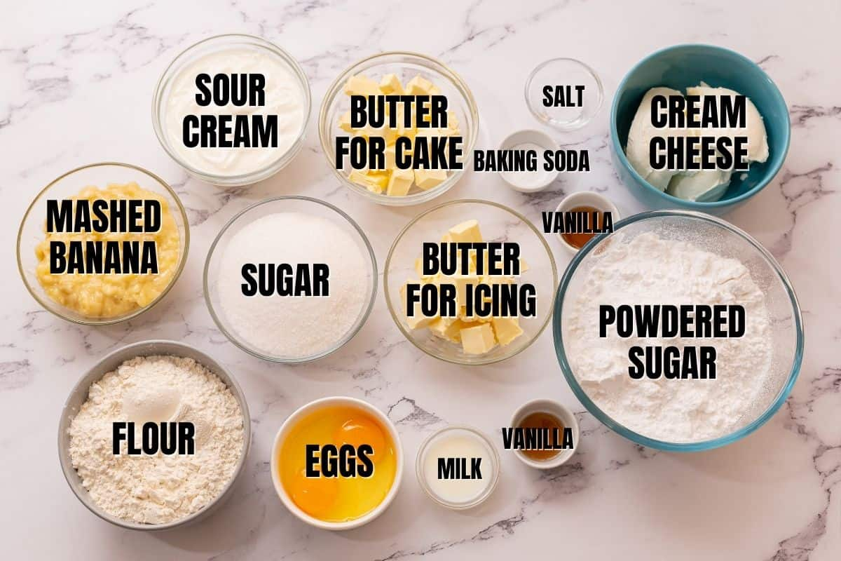Ingredients labeled for banana cake and cream cheese icing on white counter.