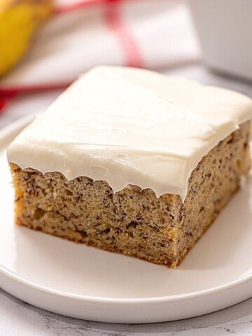 Slice of banana cake with cream cheese frosting on a white plate.