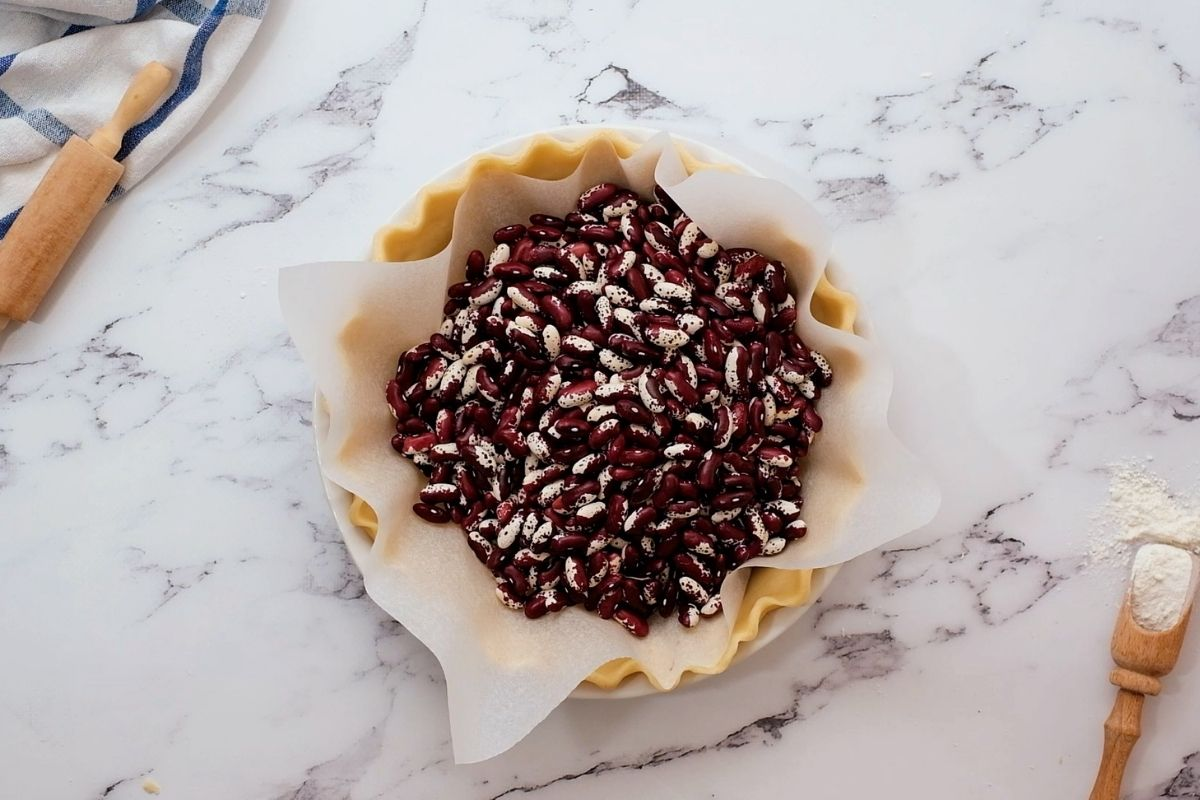 Pie crust covered with parchment paper filled with dried beans.