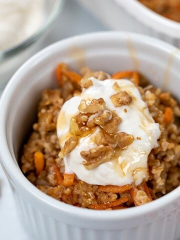 Bowl of Carrot Cake Oatmeal topped with nuts maple syrup and yogurt.