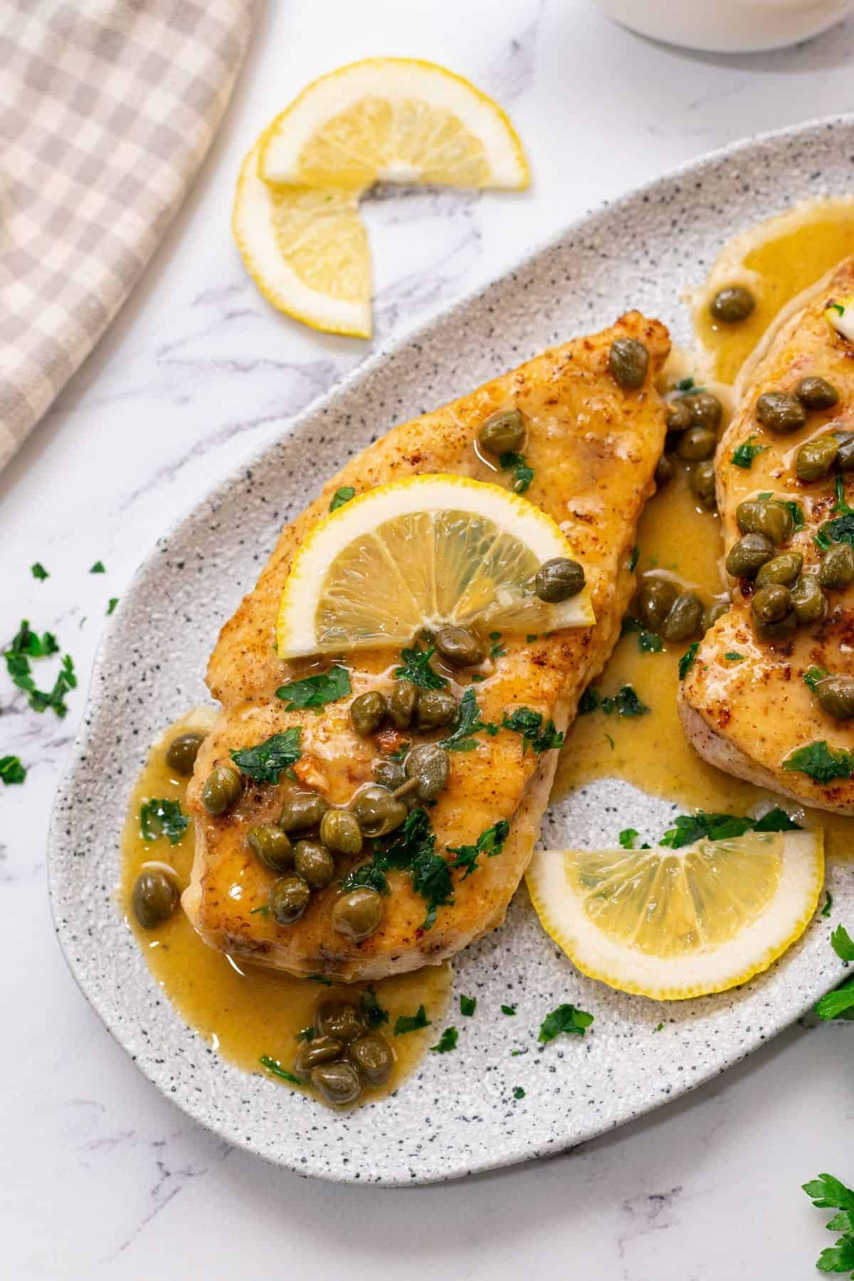 Chicken Piccata on white platter with fresh lemon slices and parsley topping the chicken.