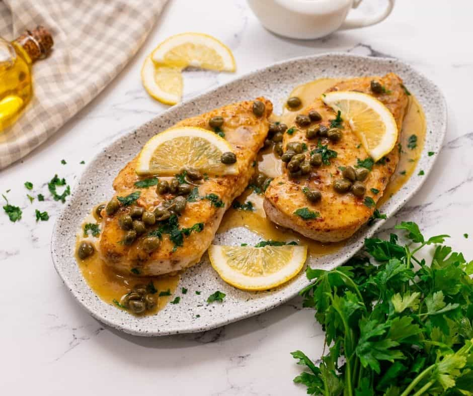 Chicken Piccata on white tray with sliced lemon and fresh parsley to the side.