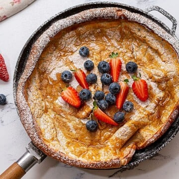 Fluffy crispy German pancake in skillet topped with berries.