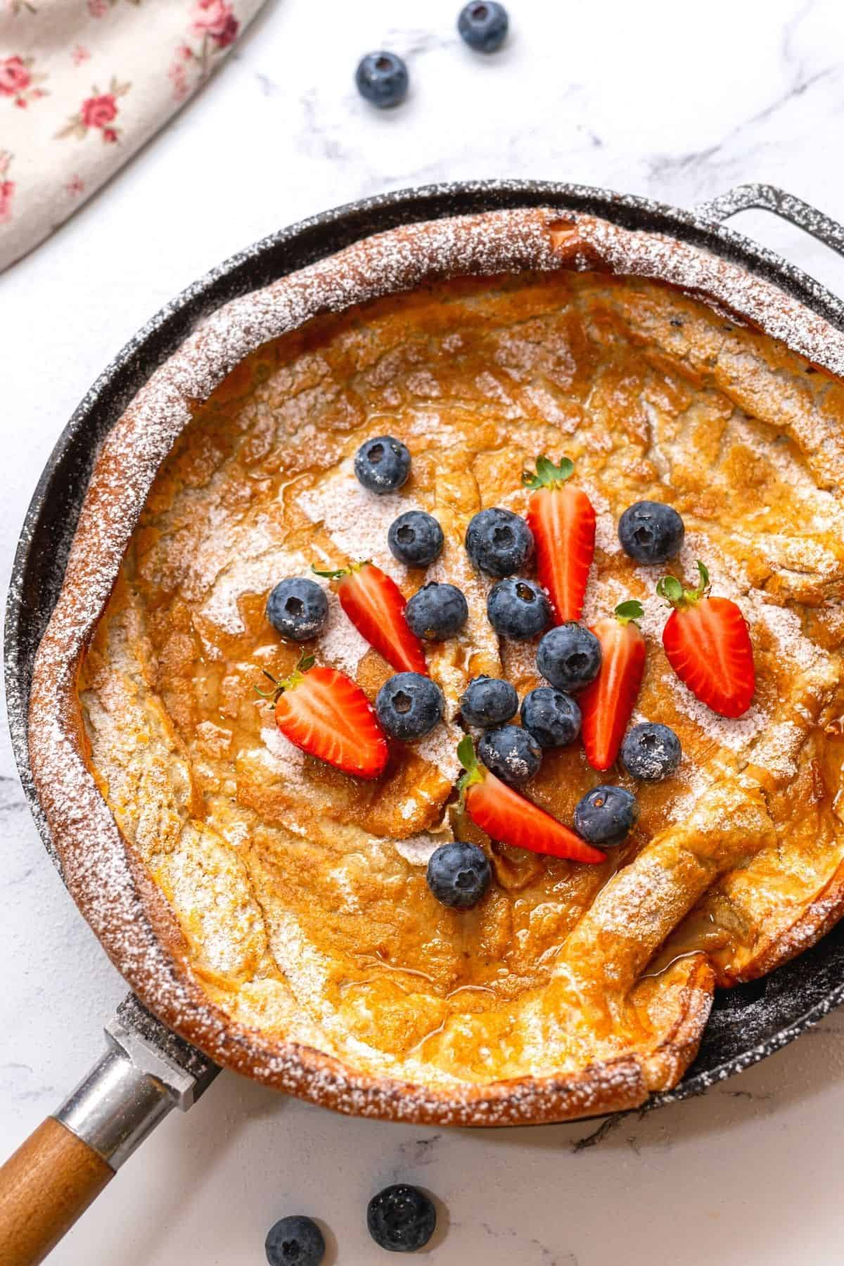 Baked Dutch Baby Pancake in cast iron skillet with topped with berries.