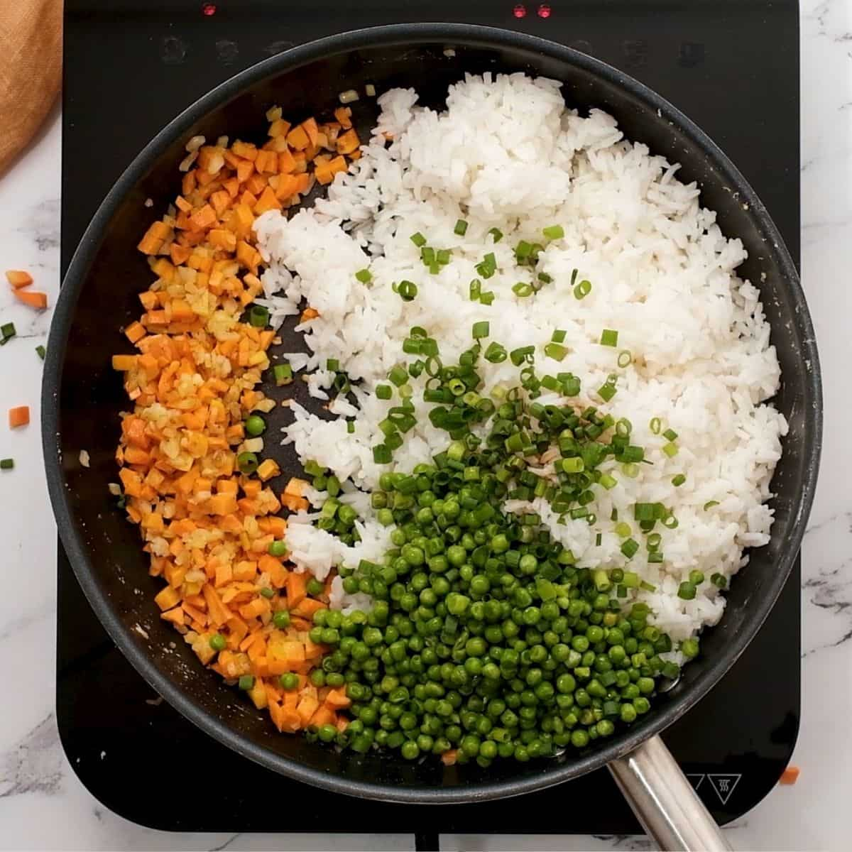 Skillet with rice, peas,and carrots.
