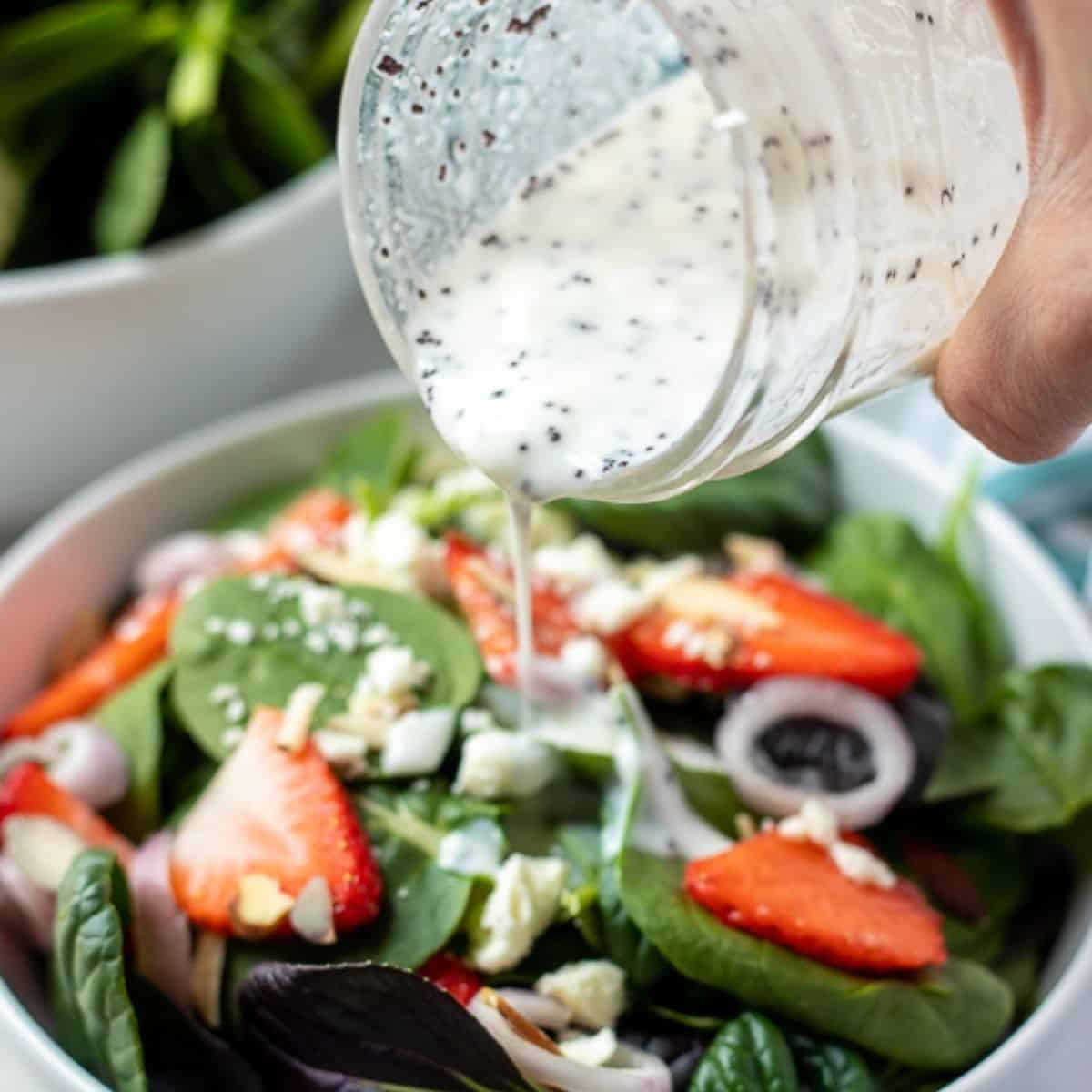 Poppyseed dressing being poured onto a strawberry spinach salad.